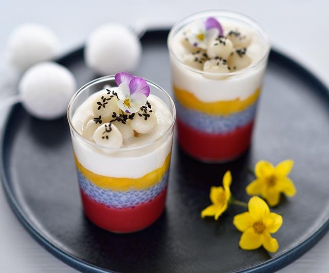 Schichtdessert im Glas mit Butterfly-Pea-Tapioka-Pudding und Klebreisbällchen