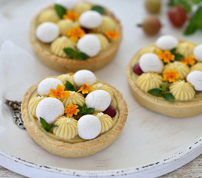 Stachelbeer-Tartelettes mit Orangen-Frischkäse-Creme und Baiser-Drops (bbbakery.at)